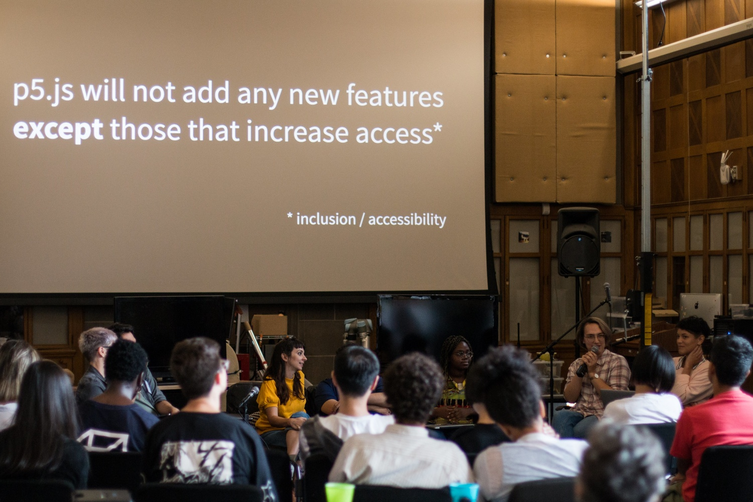 Person with a microphone speaking to fellow participants in front of text that reads p5.js will not add any new features except those that increase access