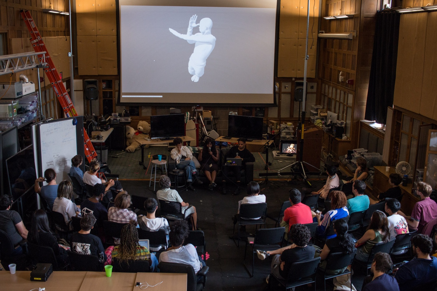 Overhead view of participants listening to a panel of people with an image of a 3d rendered man on it