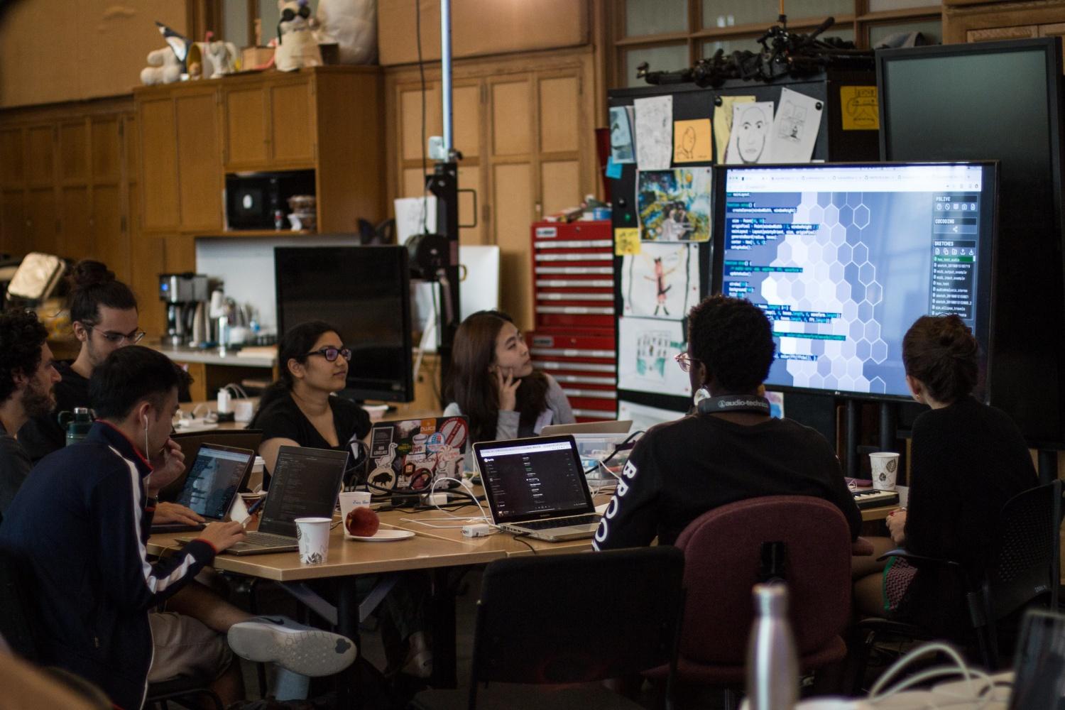 Participants sit around a table with their laptops and observe code on a screen