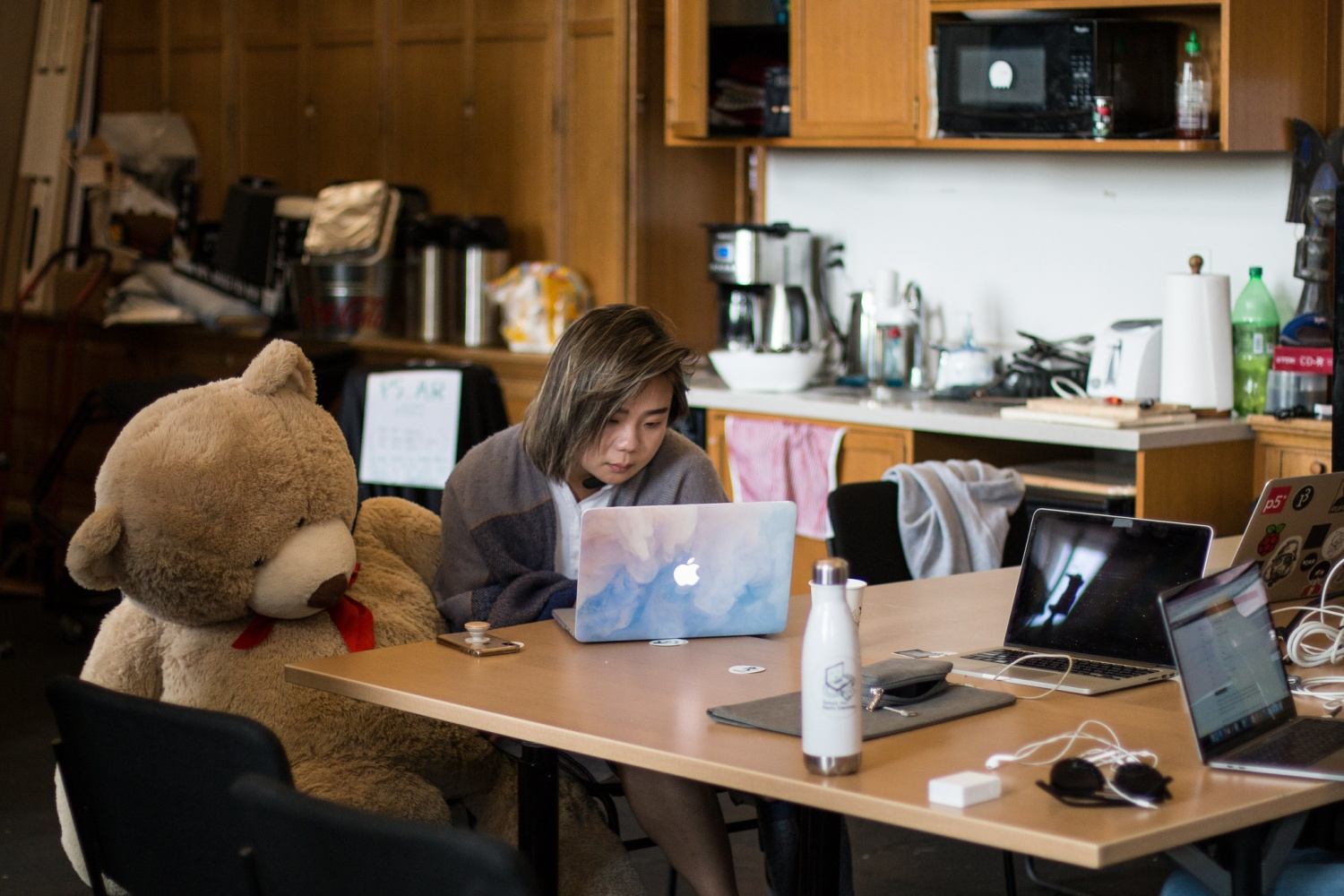 Woman sitting next to a lifesize teddy bear works on her laptop