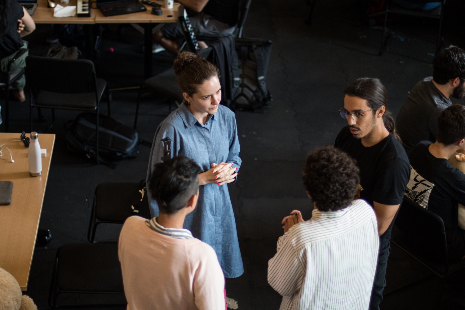 Four participants standing in a circle conversing