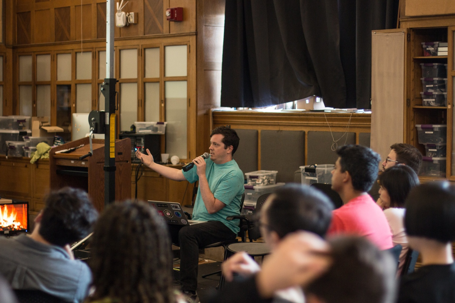 Man sitting in front of the classroom speaking energetically into a microphone