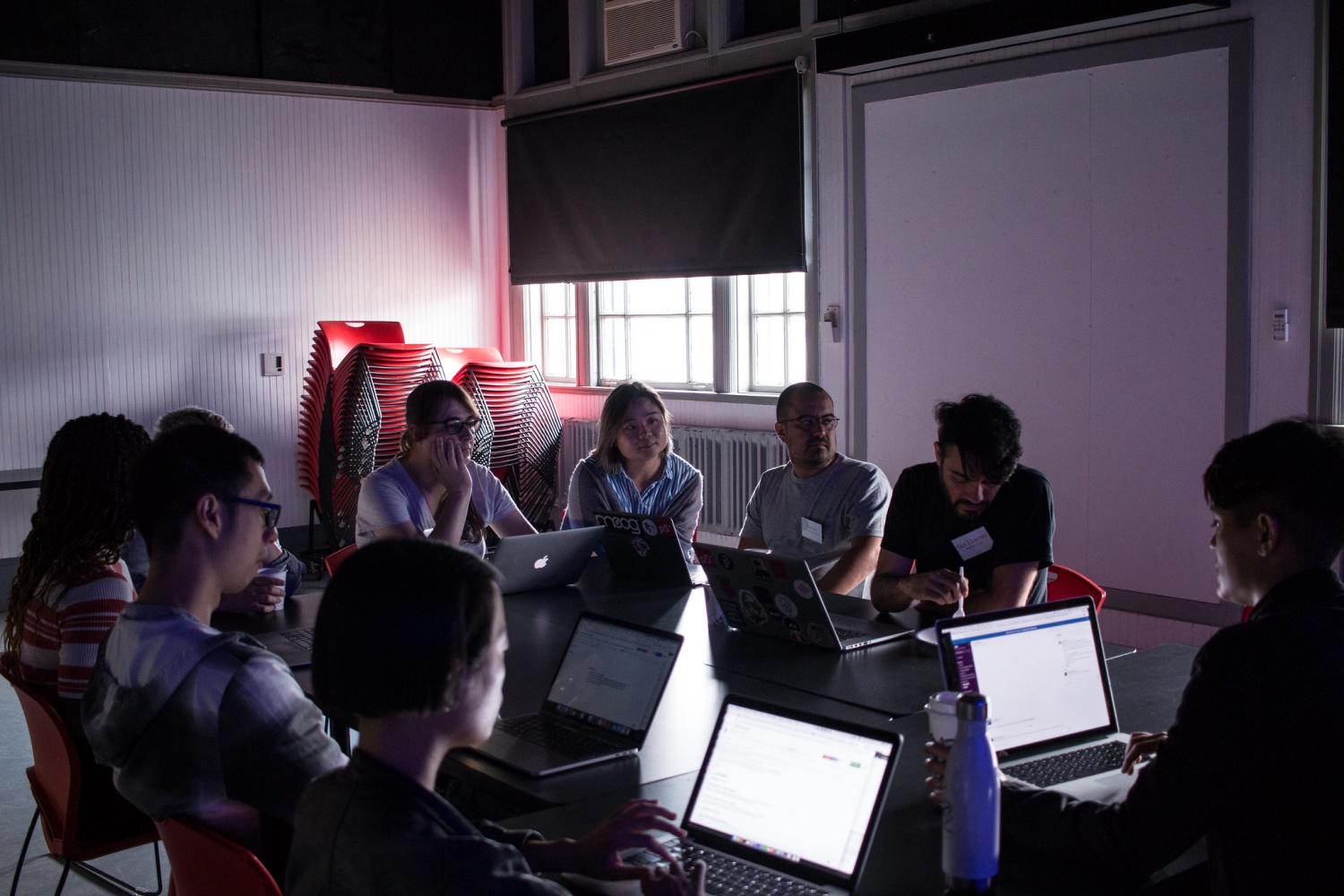 Participants in a meeting in a dark classroom