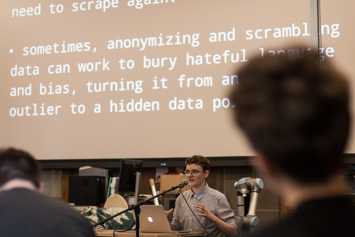 Participant speaks at a podium in front of projected text about the problem with anonymyzing data