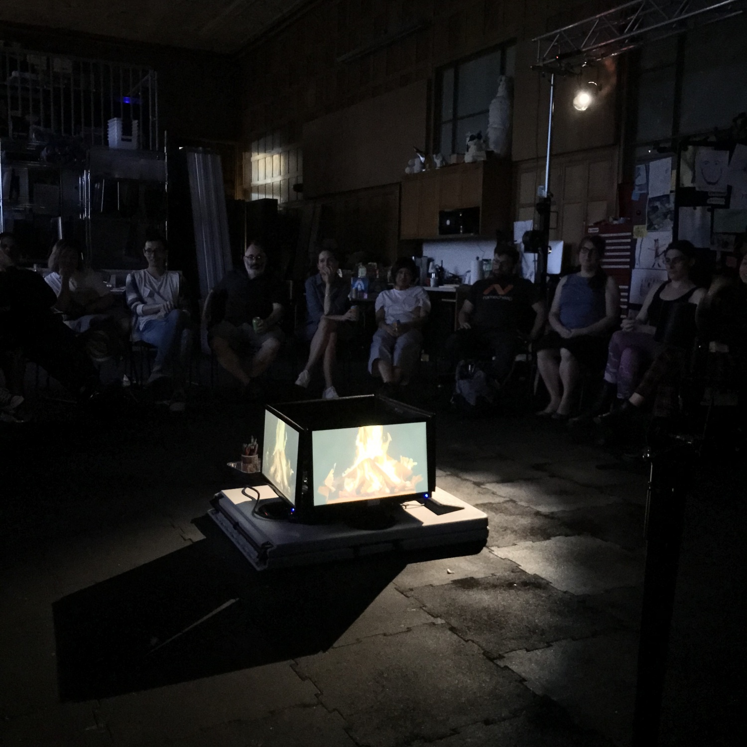 Group of people sit around campfire made from four LCD monitors.