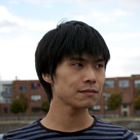 A profile of a person looking to the right. There are buildings behind them in the distance.