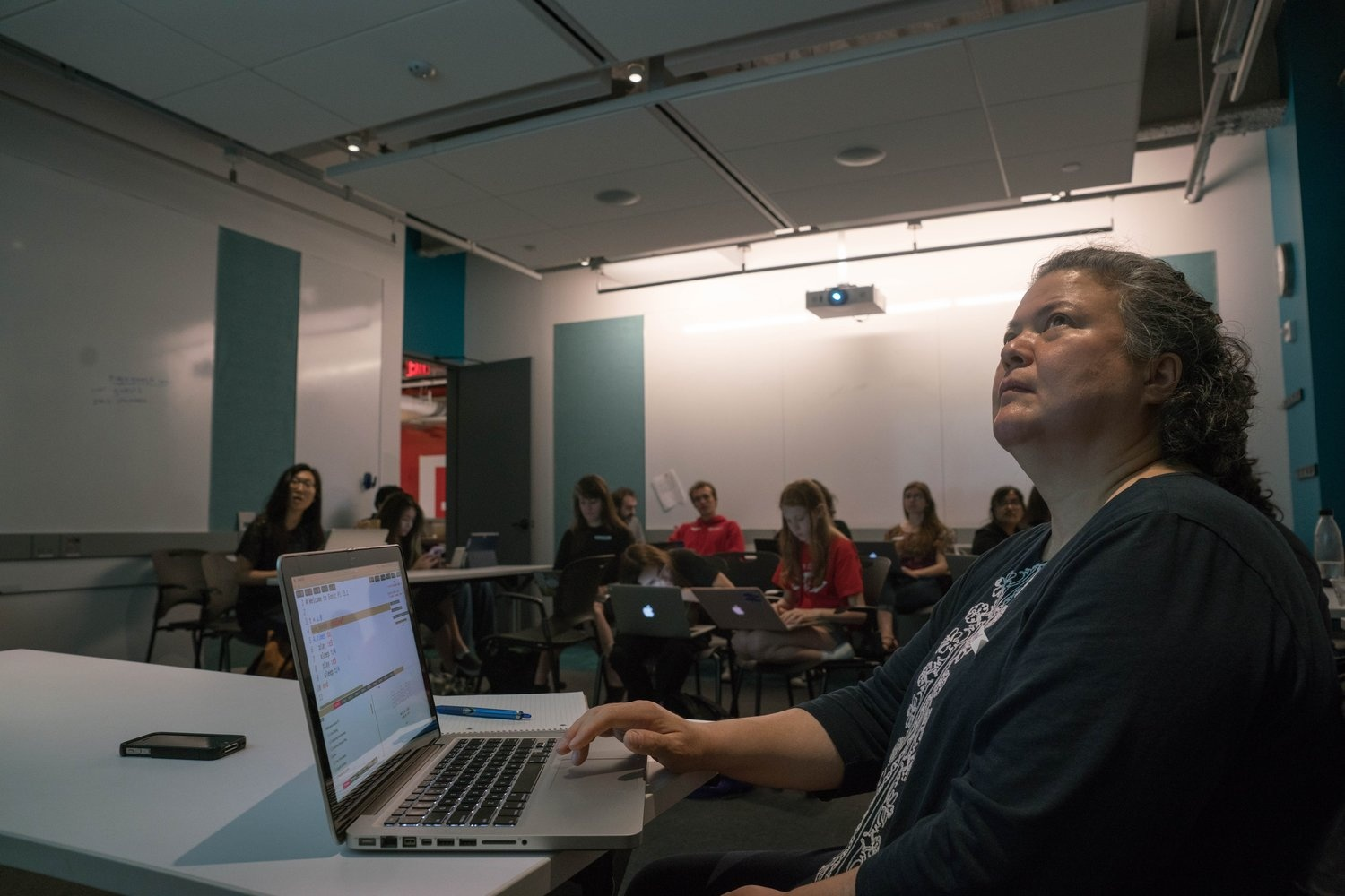 A person with a laptop looking up at the projection screen in a classroom. There a group of people sitting behind her in desks.