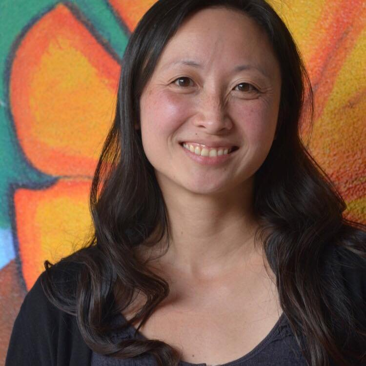 Angi, an Asian woman, is smiling at the camera. She wears a black top and has long black hair. In the background is a wall painting of a large orange flower.