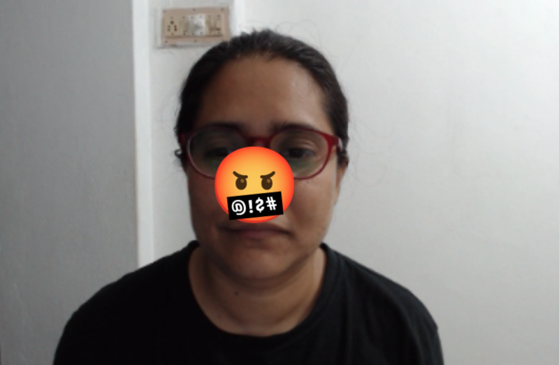 A bespectacled adult woman of Indian origin looks at the camera. The angry, cursing emoji covers part of her face.