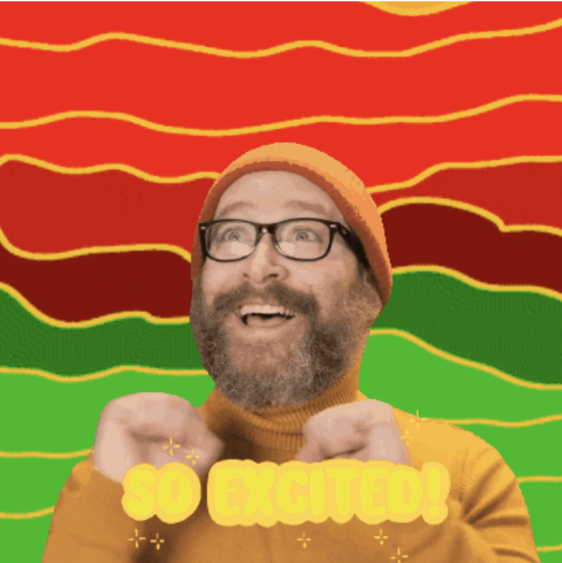 Shawn Higgins, a bearded white male with a red wool cap and black glasses shakes his hands in excitement. He wears a yellow turtleneck sweater and smiles. His beard is large and puffy, brown but flecked with grey. In front of him the words SO EXCITED flash in orange. Behind him is a rainbow of shades of red and green.