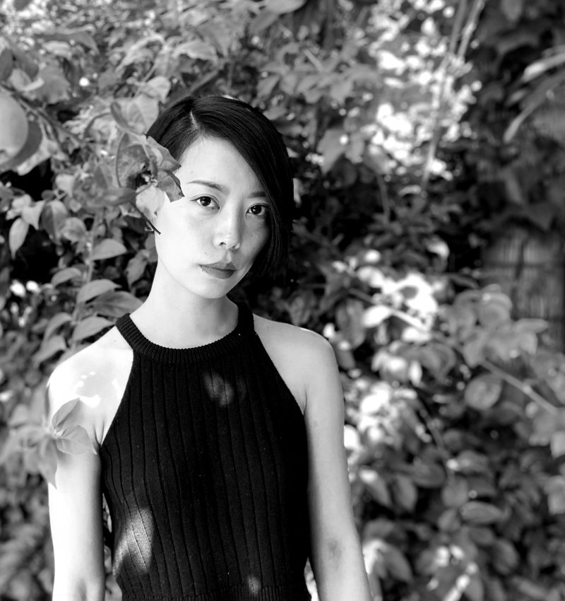 Qianqian, a non-binary Chinese person with black short hair, wearing a black tank top, standing next to an apple tree, with a lush garden in the background.